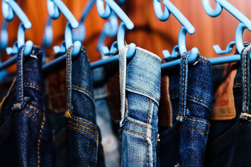 Close-up of jeans hanging on coathangers in store for sale