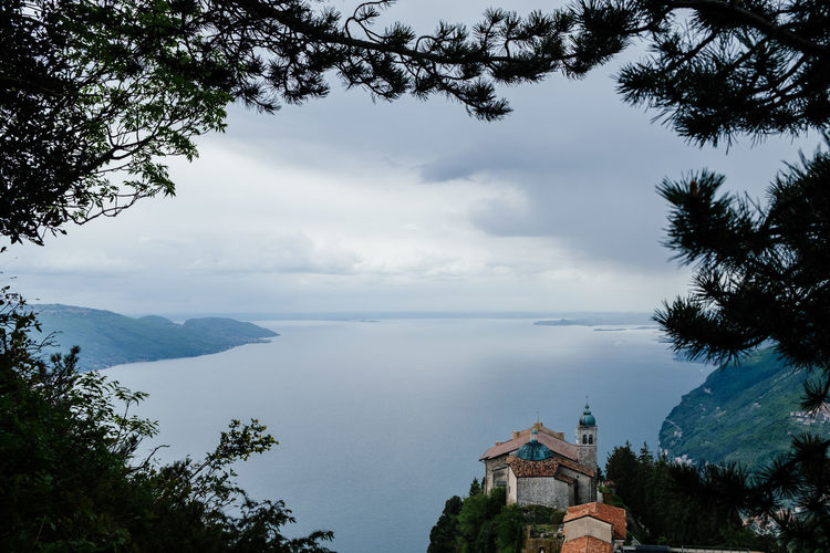 High angle view of lake garda and houses against cloudy sky