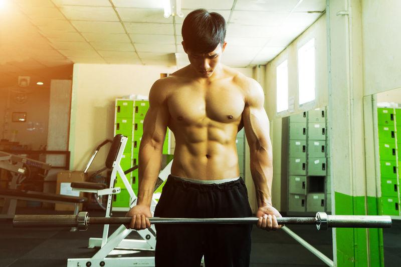 Shirtless Muscular Man Lifting Weights While Exercising At Gym