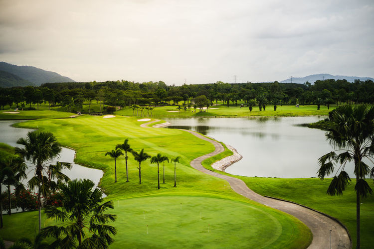 Beauty In Nature Cloud - Sky Day Golf Golf Course Grass Green - Golf Course Green Color Lake Landscape Nature No People Outdoors Plant Scenics - Nature Sky Sport Tranquil Scene Tranquility Tree Water