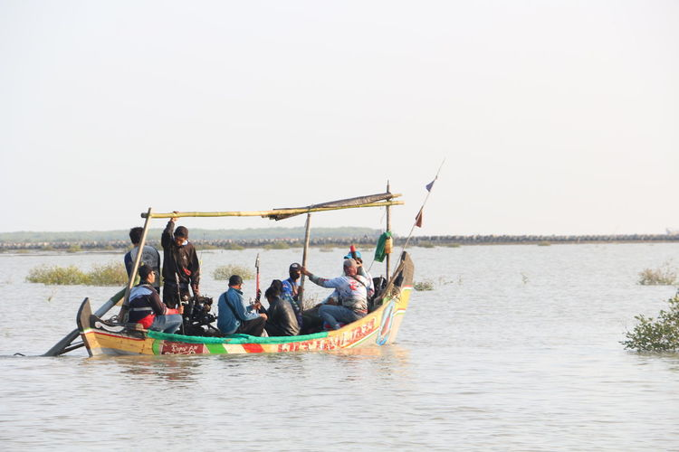 People in boat on lake against clear sky