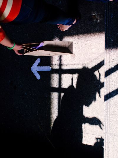 Low section of man with shadow on road