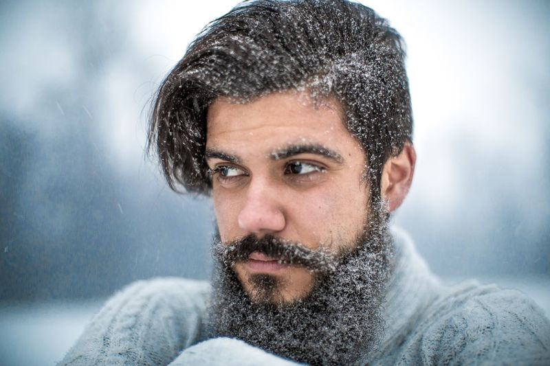 Thoughtful bearded man looking away during snowfall