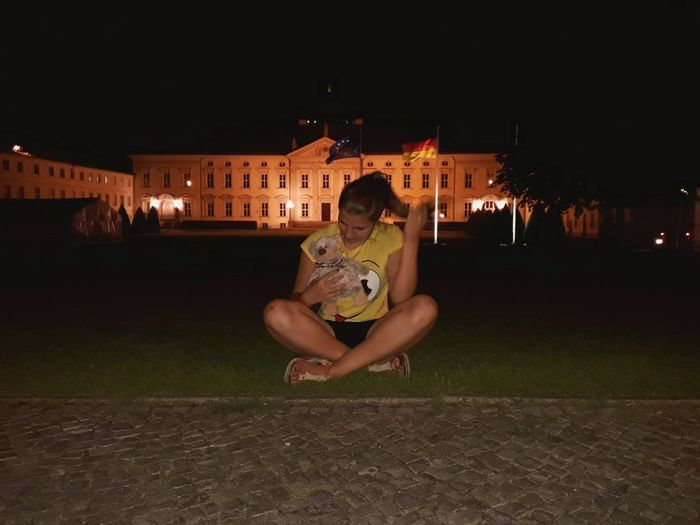 Portrait of man sitting on illuminated city at night