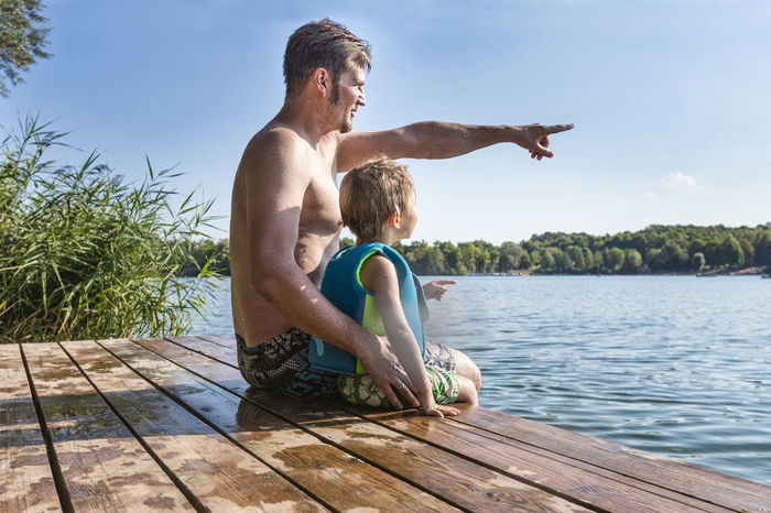 Father and son sitting togheter on a lake Adult Care Child Childhood Enjoy Family Father Friendship Fun Happiness Holiday Lake Leisure Activity Love Nature Outdoors Showing Son Summer Swimming Together Togetherness Vacations Vacations Water