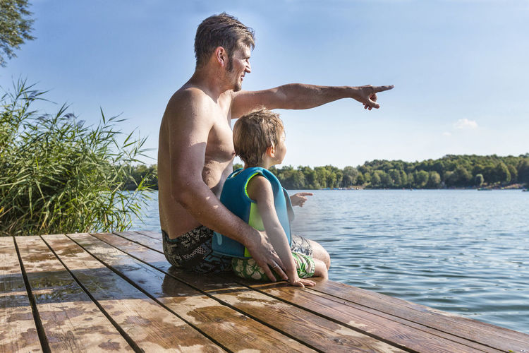 Father pointing while sitting with son on wet pier over lake against sky