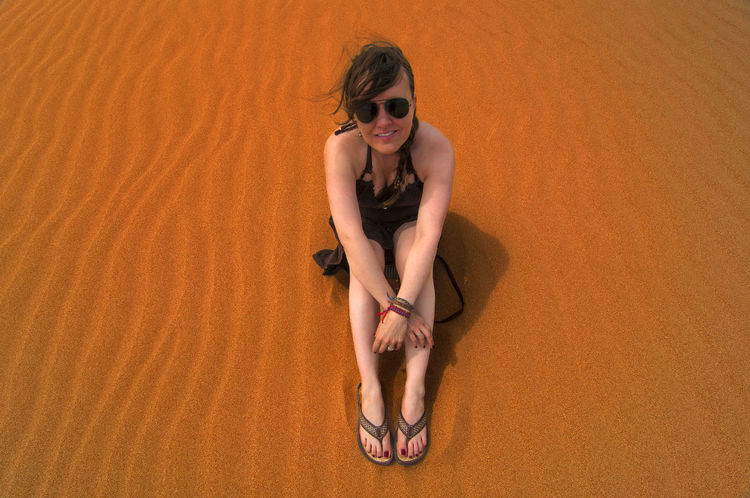 Caucasian woman sitting in sand on top of a sand dune. Adult Arid Beach Coast Day Desert Dunes Female Girl Horizontal Hot Landscape Natural Nature Outdoors Outside People Sand Sandy Scenic Sunny Tourism Travel Vacation Wilderness