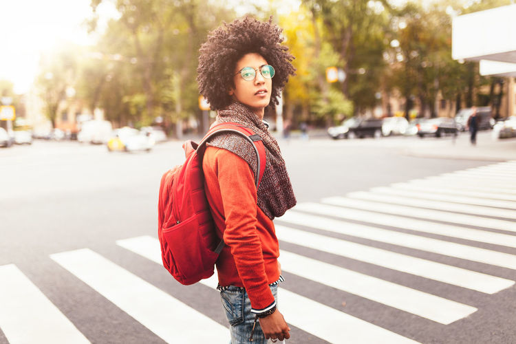 Side View Portrait Of Young Man Carrying Backpack While Standing On Street During Sunny Day