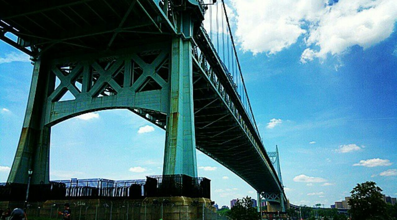 bridge - man made structure, connection, architecture, engineering, built structure, low angle view, sky, transportation, cloud - sky, suspension bridge, outdoors, day, travel, travel destinations, city, chain bridge, no people