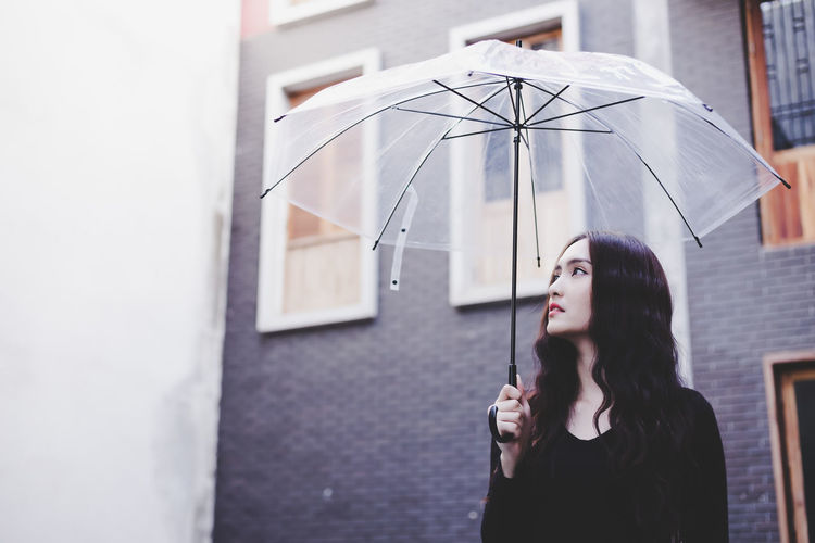 Young woman standing with umbrella against building