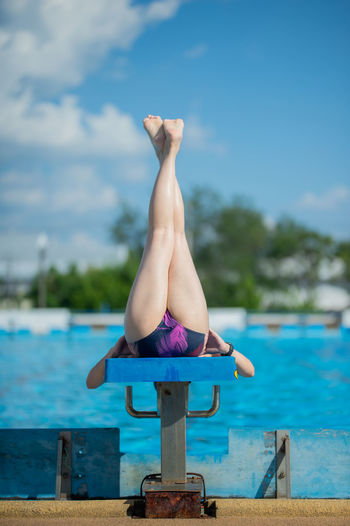 Woman exercising at poolside against sky