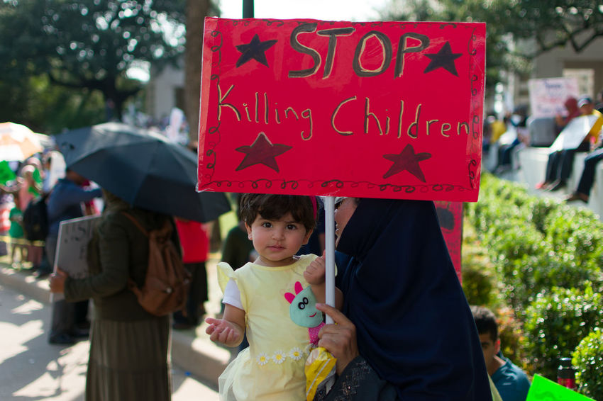A little girl with her mother at a protest in Dallas TX to draw attention to the US support of the Myanmar government who are currently slaughtering Rohingya Muslims Child Children Only Girls People Outdoors Two People Childhood Day Red Adult Dallas Muslim Culture Muslim Woman Rohingya Myanmar Young Women Muslim Protest Muslims Protestors Only Women