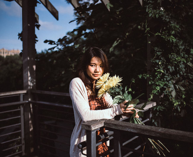 Young woman standing with flowers by railing against trees