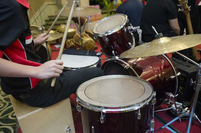 Midsection of musician playing drum kit
