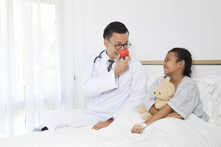 Playful doctor sitting with girl on bed at hospital