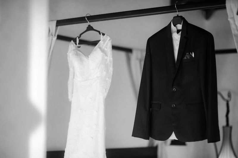 Wedding dress and suit hanging from rack