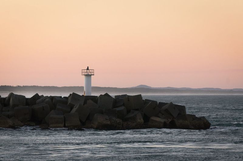 Lighthouse on pier at sea against sky during sunset
