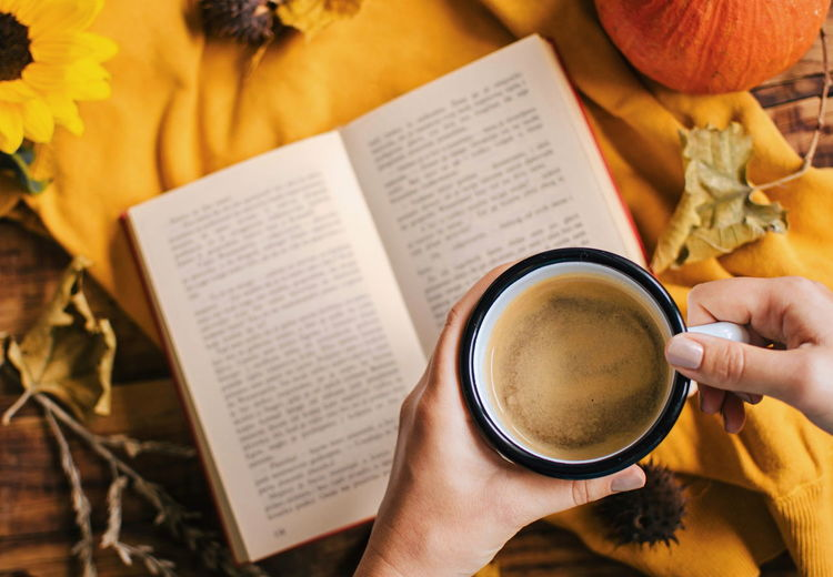 Holding a cup of coffee over a book.