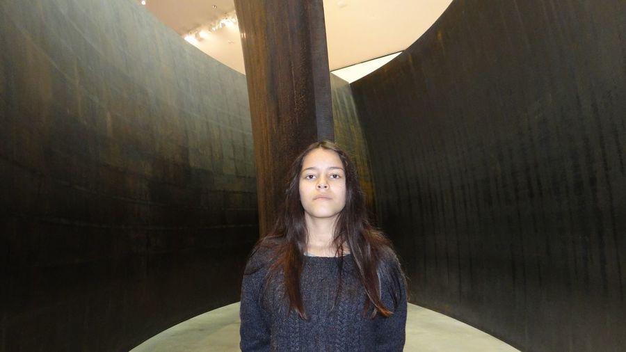 Portrait Of Teenage Girl Standing Against Column In Building