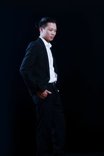 Man in full suit standing against black background
