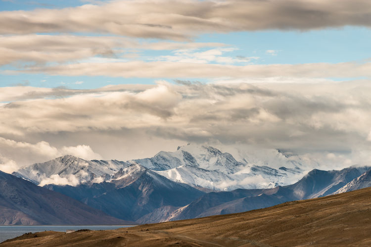 Scenic view of mountains against cloudy sky on sunny day