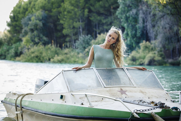 Attractive blond girl with long curly hair wearing a short green summer dress on a small old boat. Young woman with a natural background at lake. Adult Blond Hair Day Front View Hair Hairstyle Happiness Leisure Activity Lifestyles Mode Of Transportation Nature Nautical Vessel One Person Outdoors Smiling Transportation Travel Water Women Young Adult