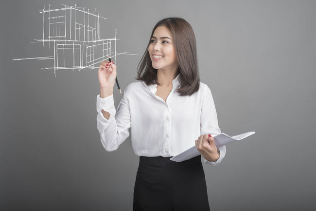 Adult Beautiful Woman Blackboard  Business Drawing - Activity Gray Background Holding Home Home Interior Indoors  Long Hair Looking At Camera Model Home Occupation One Person One Woman Only One Young Woman Only People Portrait Smiling Standing Women Writing Young Adult Young Women
