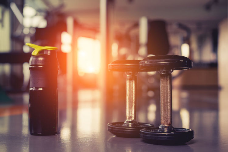 Close-up of water bottle and dumbbells on floor in gym