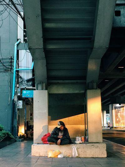 Beggar sitting under bridge