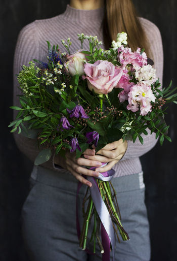 Woman holding bouquet of flowering plant