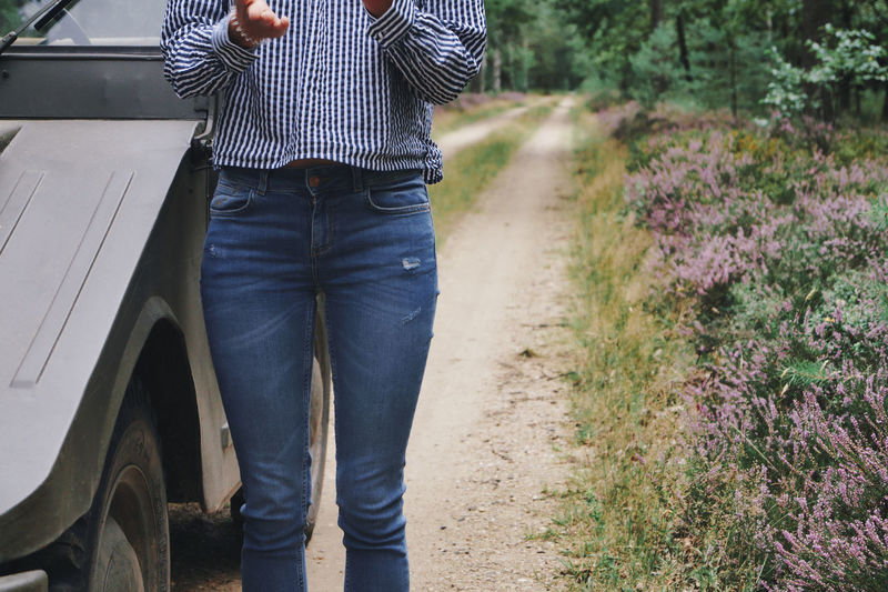 Midsection of woman standing on land by car and plants