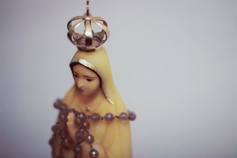 High Angle View Of Virgin Mary Figurine Against Wall