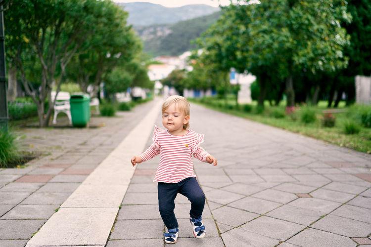 Full length of cute girl on footpath