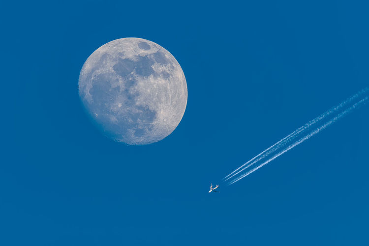 Low angle view of moon and vapor trail in sky