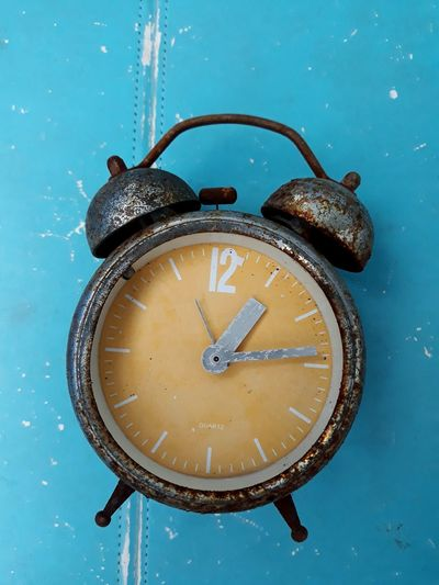 Directly above shot of weathered clock on blue table