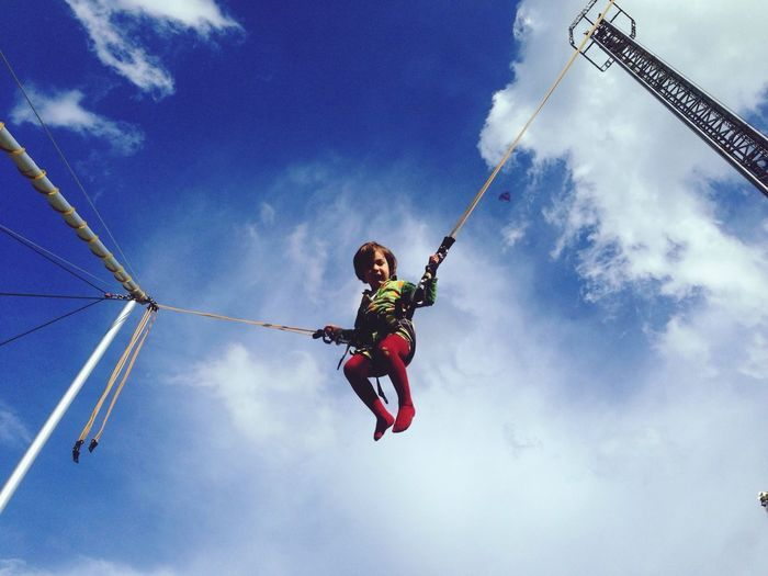 Low angle view of girl jumping against cloudy sky