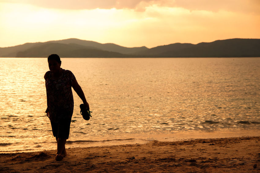 silhouette of people at the beach,The beauty of natural light at sunset. Sunset Real People Sky Water Beauty In Nature Beach Sea Lifestyles Leisure Activity One Person Rear View Silhouette Land Scenics - Nature Full Length Standing Nature Orange Color Outdoors Silhouette Happiness Happy People Holiday Relaxing Children Women Man Romantic Orange Clouds And Sky Love Family Summer Sunrise Boy Freshair Freedom Fun