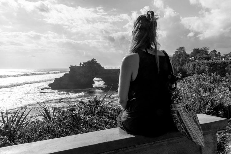 Rear view of woman sitting on bench while looking at batu bolong temple in sea against sky