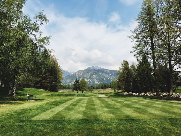Scenic view of golf course against mountain peak