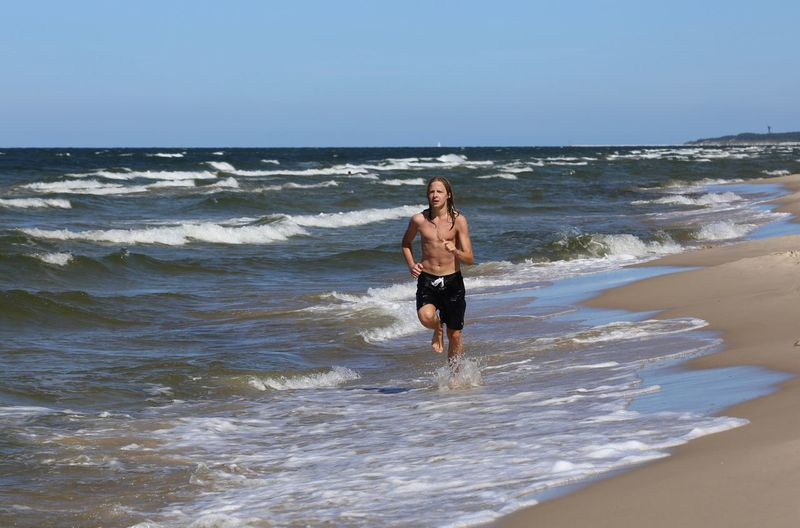Shirtless teenager running on shore at beach against sky