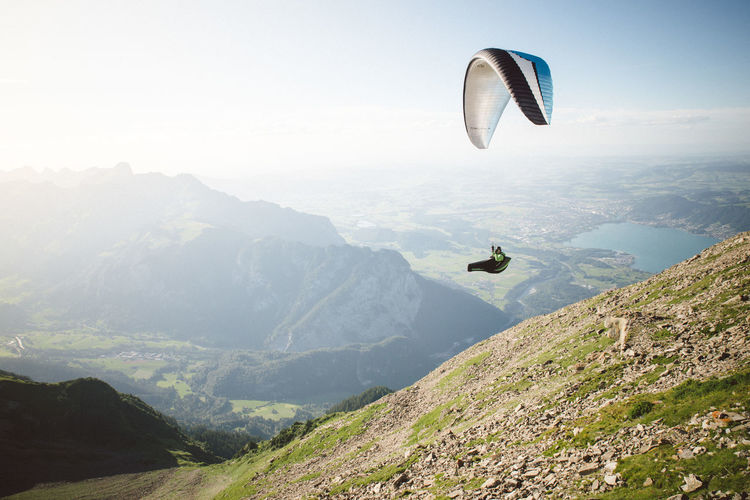 View of man paragliding over landscape against sky