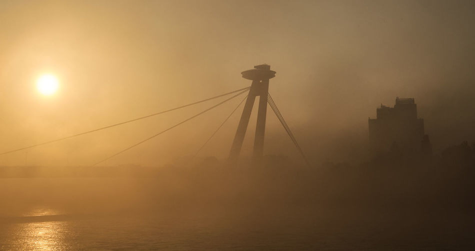 The SNP bridge in Bratislava during a misty morning Fog Sky Water Architecture Silhouette No People Built Structure Sun Nature City Outdoors River Transportation Building Exterior Waterfront Beauty In Nature Cityscape Skyscraper Sunrise Bridge Bridge Pylon Misty Morning Mist
