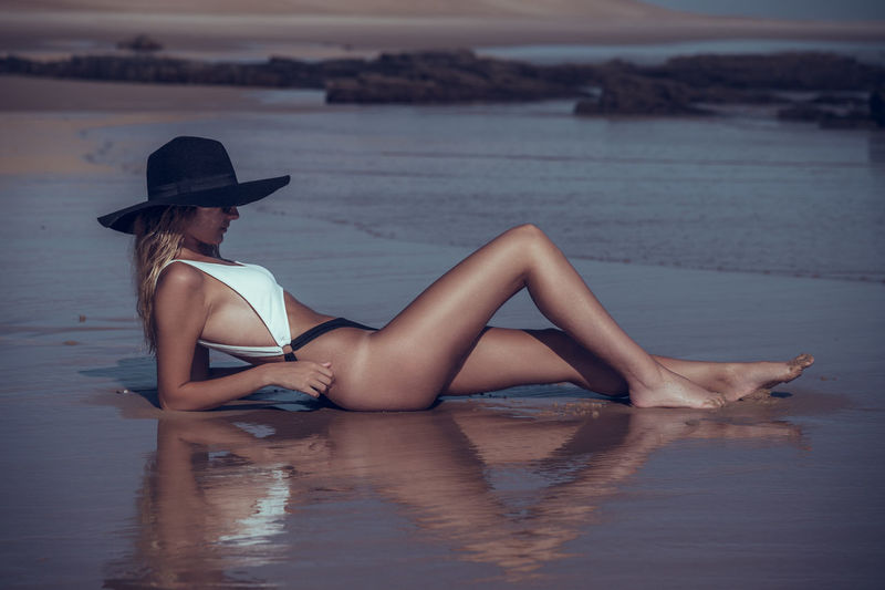 Side view of woman in bikini reclining on shore at beach