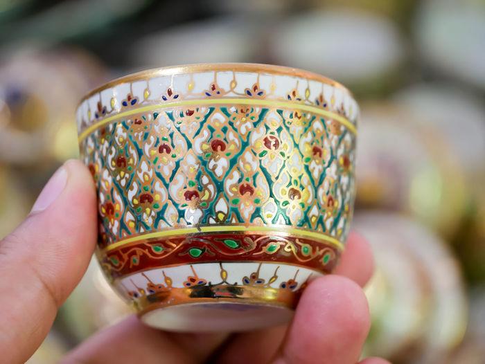 Thai Benjarong Ceramics Thai Benjarong Cup Benjarong EyeEm Selects Human Hand Holding Gold Colored Cultures Tradition Human Finger Close-up Food And Drink Tea Cup
