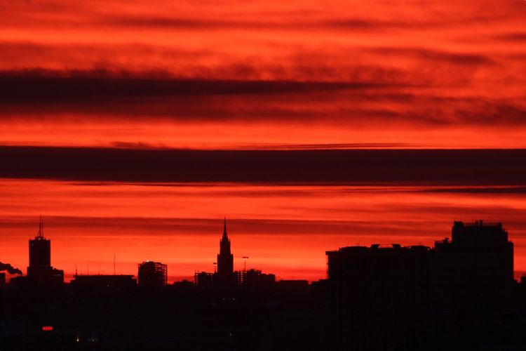 Silhouette of buildings against cloudy sky at sunset