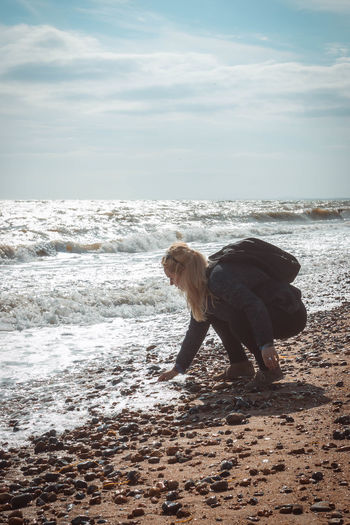 Side View Of Woman Crouching On Shore At Beach