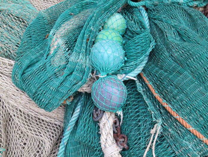 turquoise colored fishing nets and floats Rope Fishing Net No People Tied Up Fishing Industry Close-up Day Buoy Commercial Fishing Net Blue Backgrounds Outdoors Tangled Turquoise Colored Pattern Netting Fishing High Angle View Floats