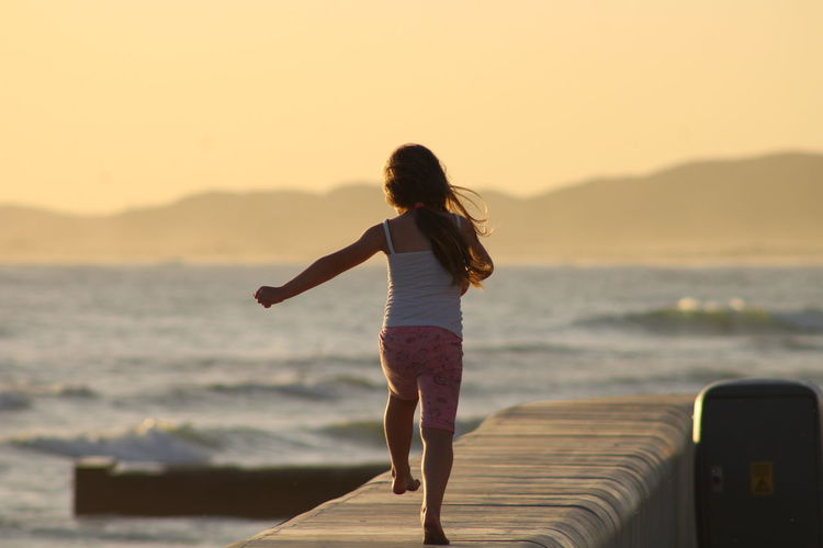 Rear view of girl walking on promenade by sea beach during sunset