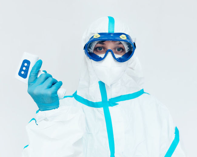 Portrait of man wearing mask against white background