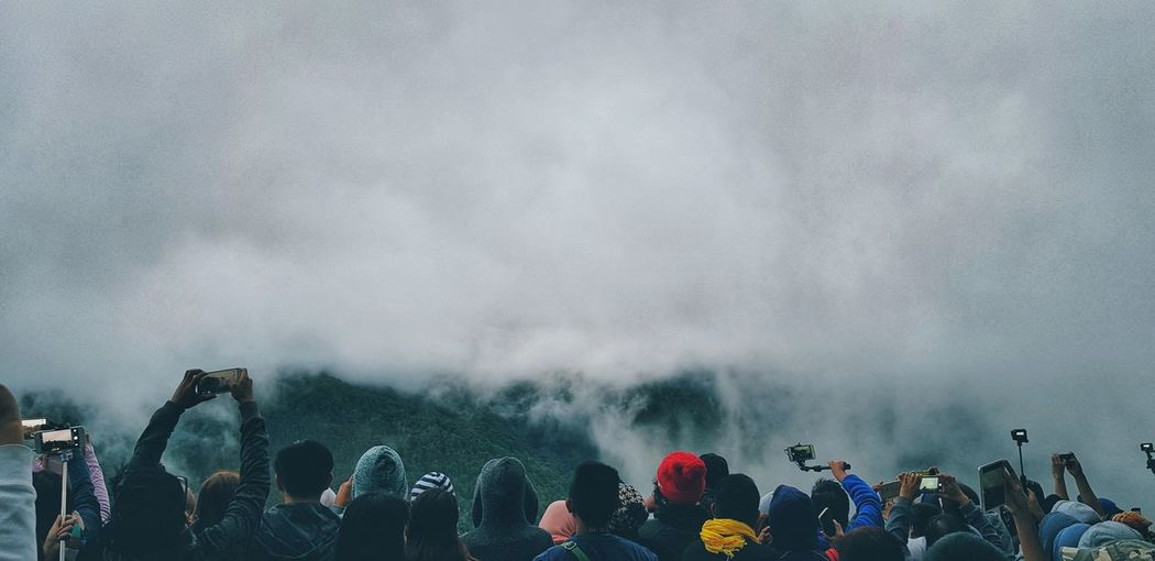 Hikers against foggy sky
